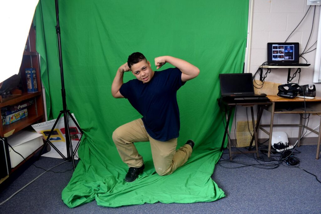 student posing in front of a green screen